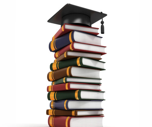 photo of a pile of books and a graduation cap on top