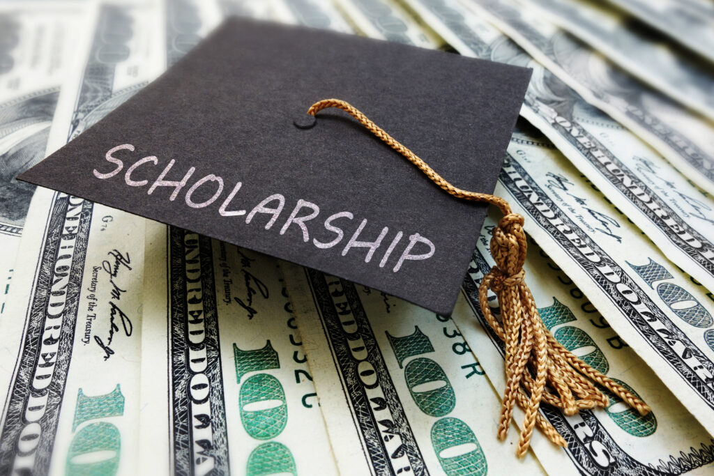 Scholarship money with a small graduation cap