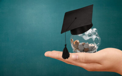 hand holding money with college graduation cap